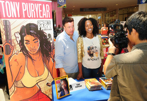creenwriter and comic book creator Tony Puryear and his wife, actress Erika Alexander, pose for a picture for a fan at his booth at the Leimert Park Village Book Fair Aug. 3. (Photo by Cynthia Gibson)